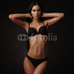 Slim beautiful model with dark straight hair, almond-shaped eyes and tanned skin in the black basic underwear collection is posing in the studio on the black background